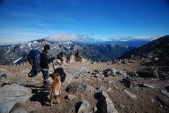 Backpacker and a dog in the outdoors. A backpacker enjoying the views of the mountains of Nahuel Huapi, Argentina Royalty Free Stock Photography
