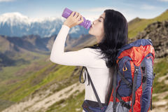 Backpacker drinks water on the mountainside Stock Photography