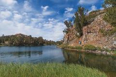 Backpacker en rastro por el lago de la montaña Imagen de archivo
