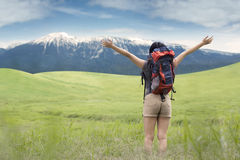Backpacker enjoying fresh air on meadow Stock Photo