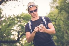 Portrait of young tourist guy looking at smartphone in nature. Backpacker finding location by using app on his mobile phone. Vacation and travel concepts Royalty Free Stock Photo