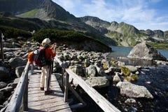 Backpacker girl exploring the mountains. Backpacker girl tourist exploring the Tatra mountains national park, Poland Stock Photos