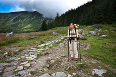Backpacker girl exploring the mountains. Backpacker girl tourist exploring the Tatra mountains national park, Poland Royalty Free Stock Photography
