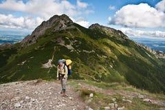 Backpacker girl exploring the mountains. Backpacker girl tourist exploring the Tatra mountains national park, Poland Stock Image