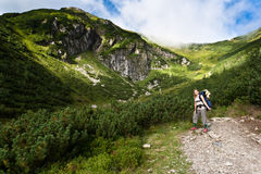 Backpacker girl exploring the mountains. Backpacker girl tourist exploring the Tatra mountains national park, Poland Royalty Free Stock Images