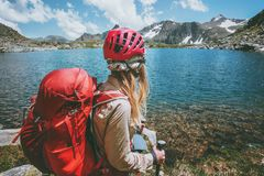 Backpacker girl hiking at blue lake in mountains with red backpack Travel Lifestyle adventure. Concept summer vacations outdoor exploring wild nature Royalty Free Stock Images