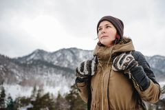 Young woman in the winter mountais. Backpacker girl listening the music in the mountains in winter royalty free stock photos
