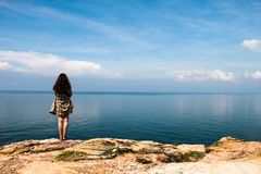 Landscape girl stands on the viewpoint of the vast ocean. Backpacker girl stands on the viewpoint of the vast ocean royalty free stock photos