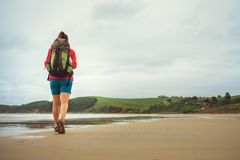 Backpacker girl traveler walk on deserted ocen beach Stock Image