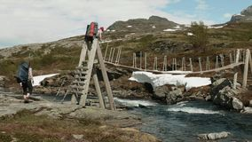 Backpacker goes on the bridge through the river in Norway stock footage