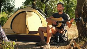 Backpacker with guitar at forest. Young man travel with guitar in a front of tent playing guitar