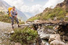 Backpacker guy crossing bridge river stream, Bolivia. Stock Photo