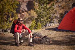 Backpacker having rest near orange tent with cup in hand. Royalty Free Stock Image