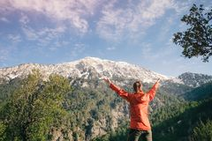 Female hiker celebrating view of Tahtali in Turkey. Backpacker with her hands raised standing next to her backpack celebrating the view of Tahtali on a sunny day Stock Photo