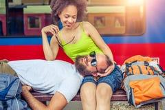 Backpacker hermoso de los pares que toma una siesta en un banco Fotos de archivo libres de regalías
