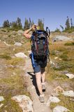 Backpacker hiking on alpine trail Stock Image