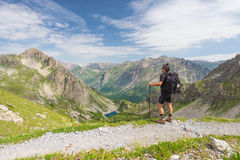 Backpacker hiking on footpath and looking at expansive view from the top. Summer adventures and exploration on the Italian French Stock Photo