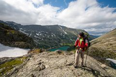 Backpacker is hiking in highlands of Altai mountains, Russia.  royalty free stock photography