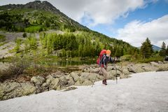 Backpacker is hiking in highlands of Altai mountains, Russia.  stock photos