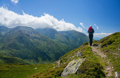 Backpacker hiking on a path in the mountains Stock Photo