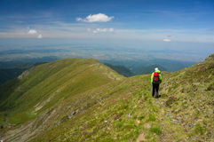 Backpacker hiking on a path in the mountains Stock Photography