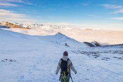 Backpacker hiking on snow on the Alps. Rear view, winter lifestyle, cold feeling, majestic mountain landscape. Backpacker hiking on snow on the Alps. Rear view Royalty Free Stock Photos