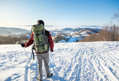Backpacker hiking on snow covered mountain Stock Photos
