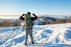 Backpacker hiking on snow covered mountain Stock Photo