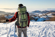 Backpacker hiking on snow covered mountain Royalty Free Stock Photo