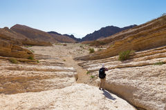 Backpacker hiking stone desert trail. Royalty Free Stock Photo