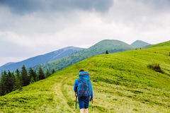 Backpacker hiking in summer mountains Stock Images