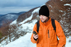 Backpacker holding GPS. Portrait of backpacker holding GPS navigator, Global Positioning System device. Mountain winter landscape as a background Royalty Free Stock Images