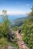 Backpacker at idyllec hiking path above garda lake Stock Images