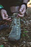 Backpacker laces boots. Backpacker laces shoes boots in forest Royalty Free Stock Photos