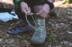 Backpacker laces boots. Backpacker laces shoes boots in forest Stock Photography
