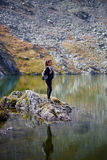 Backpacker lady hiking by the lake in the mountains Royalty Free Stock Photography