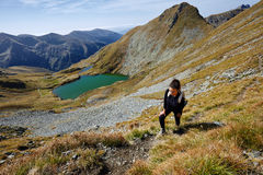 Backpacker lady hiking by the lake in the mountains Royalty Free Stock Image