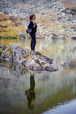 Backpacker lady hiking by the lake in the mountains Royalty Free Stock Photos