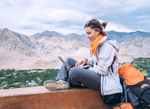 Backpacker with laptop sits on the top view point under mountain Royalty Free Stock Images