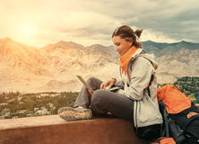 Backpacker with laptop sits on the top view point under mountain Royalty Free Stock Photo