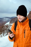 Backpacker looking at GPS. Portrait of backpacker looking at GPS navigator, Global Positioning System device. Mountain winter landscape as a background Royalty Free Stock Image