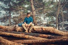 Backpacker mężczyzna obsiadanie na drewnianym bagażniku Zdjęcia Stock