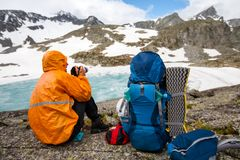 Backpacker is making photo whike resting on hike Stock Images