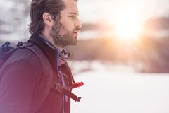 Backpacker man detail wearing anorak jacket. exploring snowy land walking and skiing with alpine ski. Europe Alps. Winter sunny day, snow, wide shot, warm sun stock photography