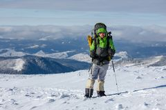 Backpacker man is posing in winter mountains Stock Image