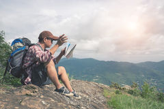 Backpacker man searching right direction on map. Royalty Free Stock Image