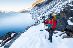 Backpacker man standing snow mountain trail above lake. Stock Images