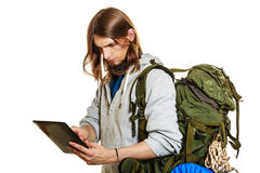 Backpacker man using pc tablet browsing internet. Royalty Free Stock Images