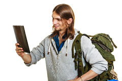 Backpacker man using pc tablet browsing internet. Stock Images