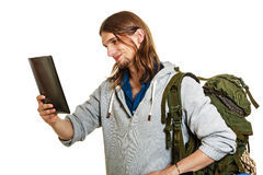 Backpacker man using pc tablet browsing internet. Stock Photo
